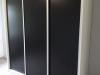 Vestavěná skříň s posuvnými černými dveřmi